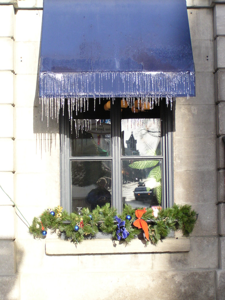 Icicles on a window awning with a reflection of Alan