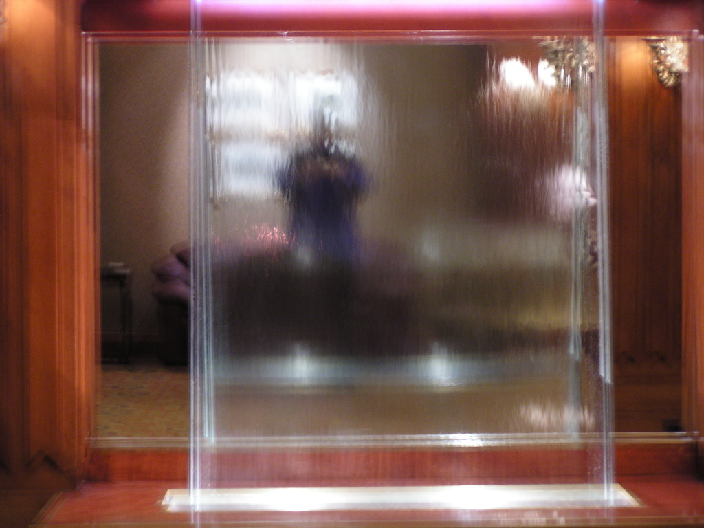 Alan reflected in the mirror behind the water sculpture in the Manoir Victoria hotel